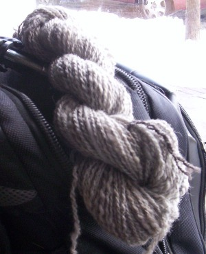 New yarn, ready to ball up and knit, resting on my bookbag in the window of Highlands Common Grounds.